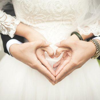 les mariés qui font un coeur avec leurs mains